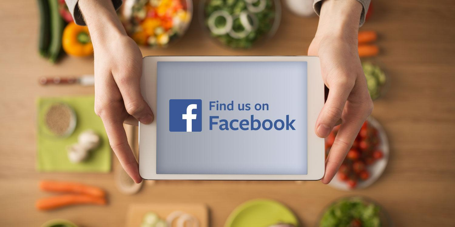 A woman holding a tablet with Find us on Facebook on the display.