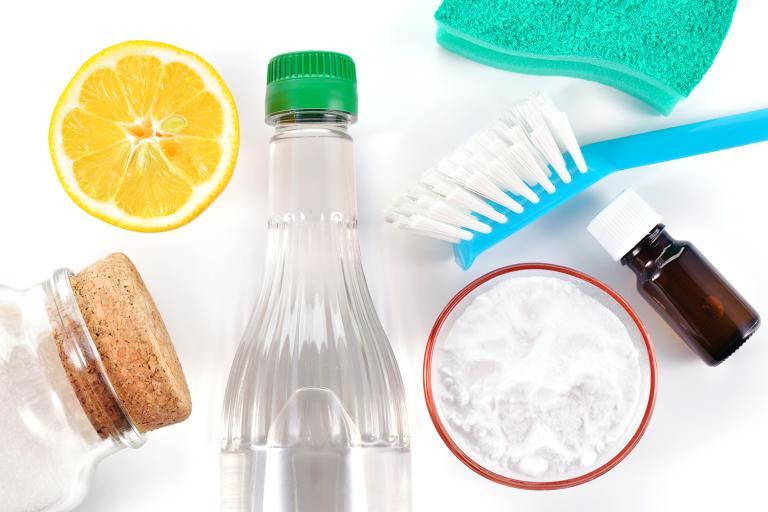 a sponge, a brush, vinegar, a lemon, baking soda, and a bottle of essential oil